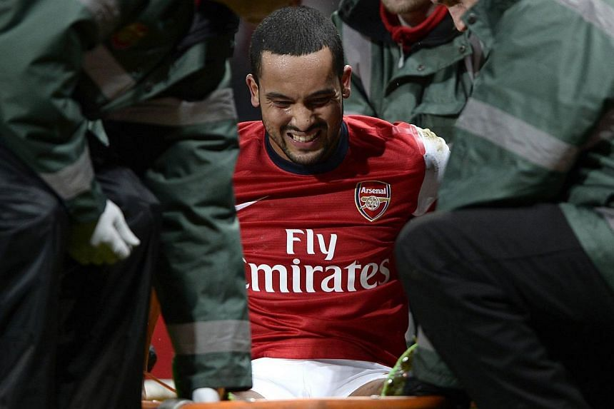 Arsenal's Theo Walcott is stretchered off the pitch during their English FA Cup soccer match against Tottenham Hotspur at the Emirates stadium in London, on Jan 4, 2014. Walcott will miss this year's World Cup in Brazil after being ruled out for at l