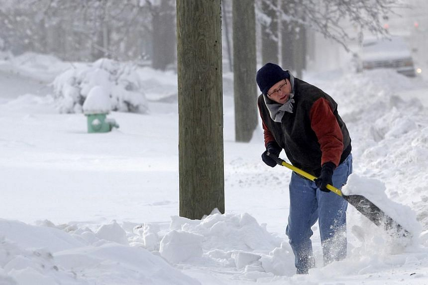 Mr Tom Zeigler shovels snow from the sidewalk in front of his home in Indianapolis, Indiana, on Jan 6, 2014. A blast of Arctic air gripped the vast middle of the United States on Monday, bringing the coldest temperatures felt in two decades, causing