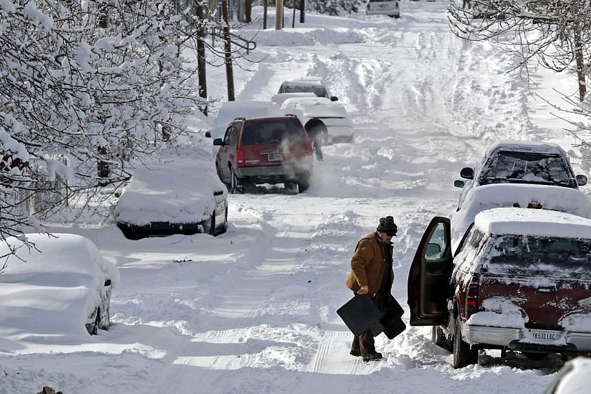 A man clears snow from his car in Indianapolis, Indiana, on Jan 6, 2014. A blast of Arctic air gripped the vast middle of the United States on Monday, bringing the coldest temperatures felt in two decades, causing at least four deaths, forcing busine