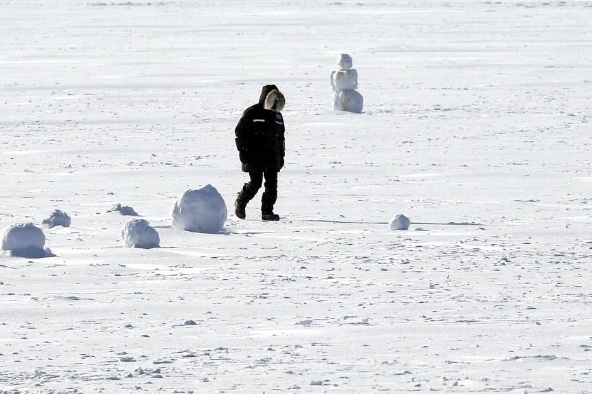 A man walks across a frozen Lake Harriet in south Minneapolis amid frigid wind chill temperatures on Jan 6, 2014. A blast of Arctic air gripped the mid-section of the U.S. on Monday, bringing the coldest temperatures in two decades, forcing businesse