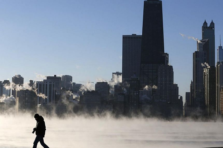 A man is silhouetted against the arctic sea smoke rising off Lake Michigan in Chicago, Illinois, on Jan 6, 2014. A blast of Arctic air gripped the mid-section of the United States on Monday, bringing the coldest temperatures in two decades. -- PHOTO: