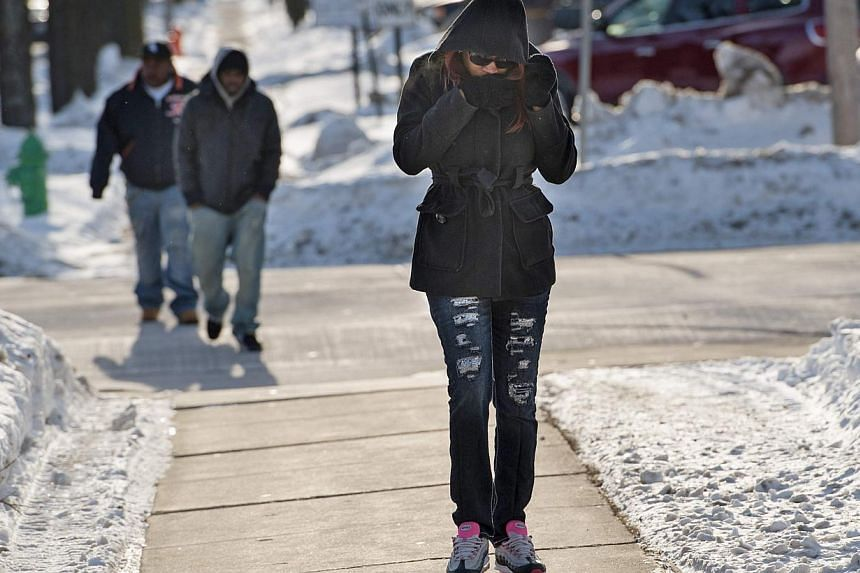 People walk into the wind outside the Brown County Courthouse in Green Bay, Wisconsin, Jan 6, 2014. Temperatures were 20 to 40 degrees F (11-22 degrees C) below average in parts of Montana, North and South Dakota, Minnesota, Iowa, Wisconsin, Michigan