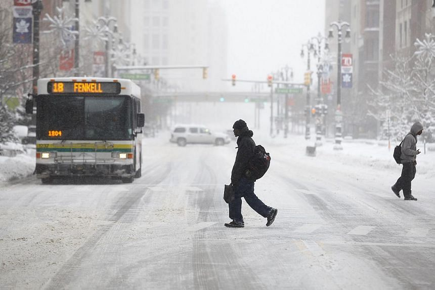 Pedestrians cross Woodward Avenue as it snows as the area deals with record breaking freezing weather Jan 6, 2014 in Detroit, Michigan. A blast of Arctic air gripped the vast middle of the United States (US) on Monday, bringing the coldest tempe
