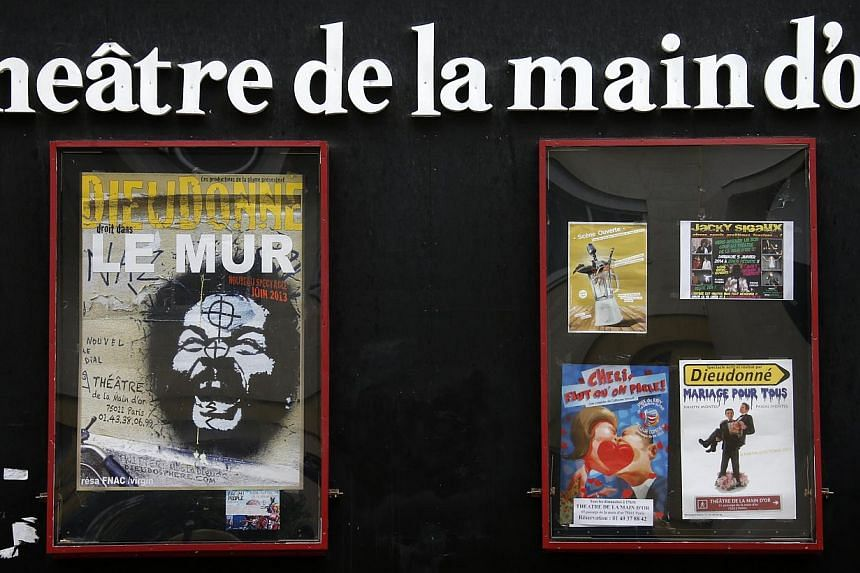 """A poster which presents the one man show named """"Le Mur"""" (L) by French comedian Dieudonne is seen in front of the Theatre de La Main d'or in Paris Dec 30, 2013.France moved on Monday to try and ban performances by the controversial comic just da"""