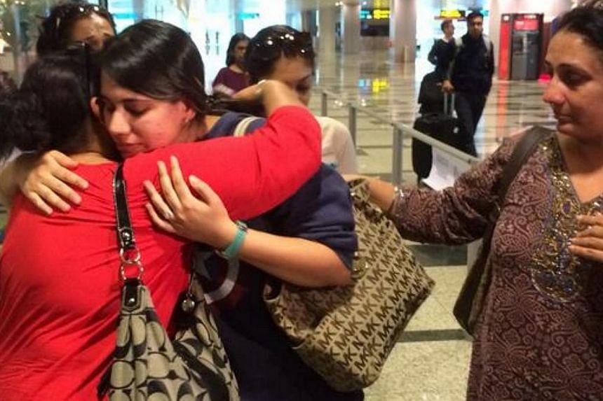 Families embrace passengers of SIA flight SQ317 as they emerge from the arrival hall at Singapore's Changi Airport. -- ST PHOTO: DERRICK HO