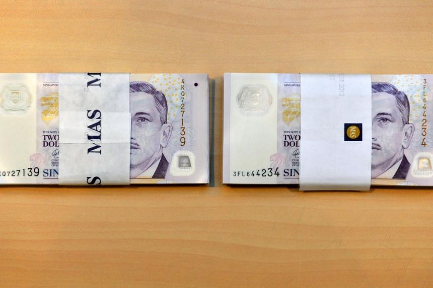 """100-piece stacks of $2 new notes (left) and """"good as new notes"""" (right). Those crisp, purple $2 notes are going green once again this Chinese New Year, with the Monetary Authority of Singapore (MAS) continuing the 'good as new' $2 notes initiative it"""