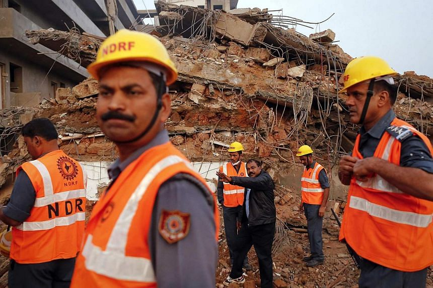 Rescue workers wait to start the day's operation to look for survivors at the site of a collapsed building that was under construction in Canacona town in the western Indian city of Goa on Jan 6, 2014. Indian police said on Tuesday they had arrested