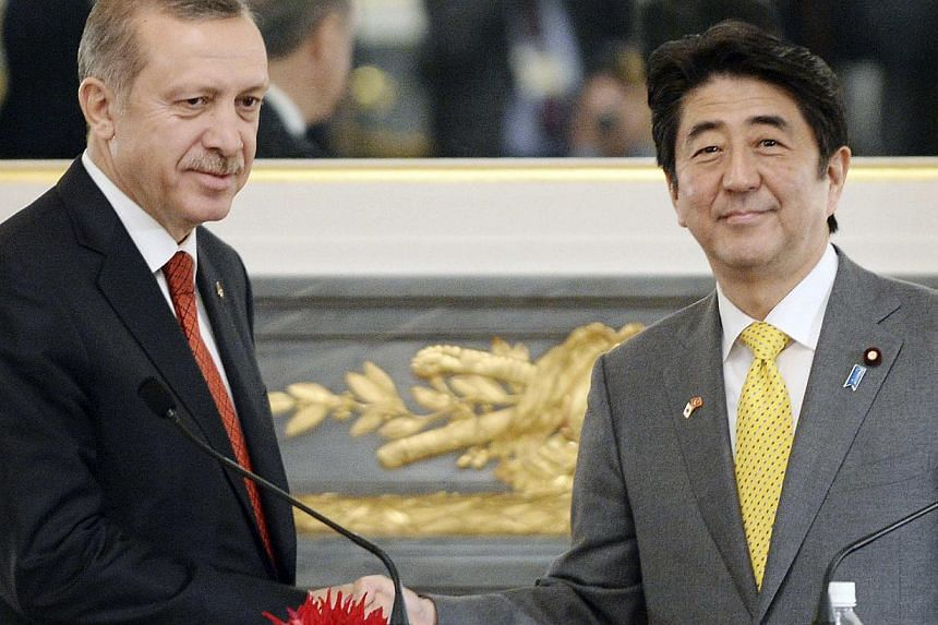 Turkey's Prime Minister Tayyip Erdogan (L) shakes hands with Japan's Prime Minister Shinzo Abe at the end of their joint press announcement at the state guest house in Tokyo on Jan 7, 2014. -- PHOTO: REUTERS
