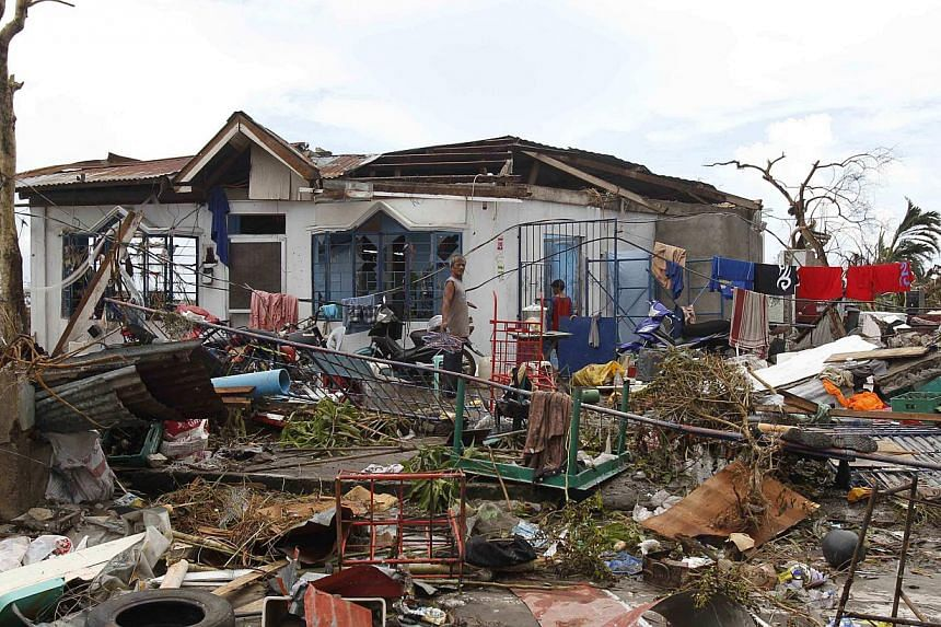 Survivors walk near their damaged house after super Typhoon Haiyan battered Tacloban city, central Philippines on Nov 9, 2013. Devastation caused by Super Typhoon Haiyan pushed inflation in the Philippines to a two-year high of 4.1 per cent in Decemb