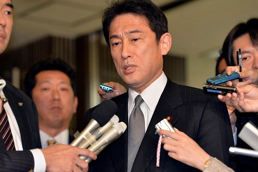 Japanese Foreign Minister Fumio Kishida (centre) is surrounded by reporters after he met with Chinese ambassador to Japan Cheng Yonghua at Kishida's office in Tokyo, on Dec 20, 2013. Japan's foreign minister left for Spain and France on Tuesday, wher