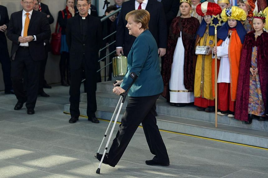 German Chancellor Angela Merkel walks with crutches upon arrival to meet with young Carol singers as part of the traditional Epiphany charity Three Kings Action at the Chancellery in Berlin on Jan 7, 2014. -- PHOTO: AFP