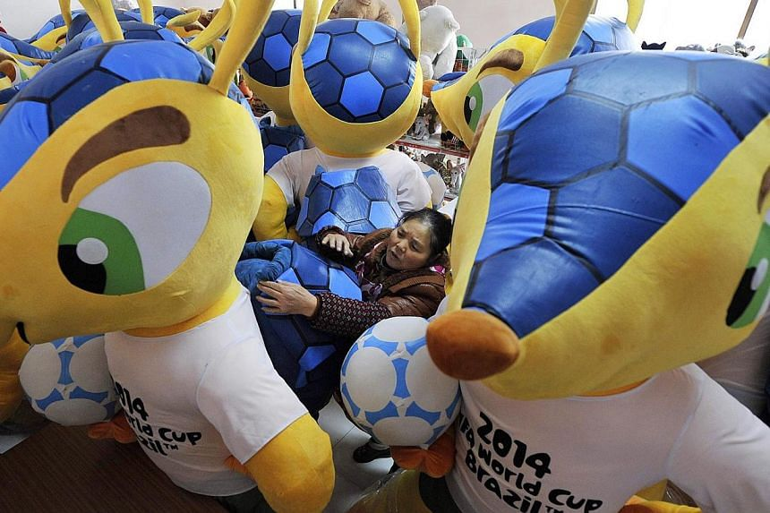 An employee adjusts a newly-made giant doll of Fuleco the Armadillo, the official mascot of the FIFA 2014 World Cup, at a factory in Anhui province, China. -- PHOTO: REUTERS