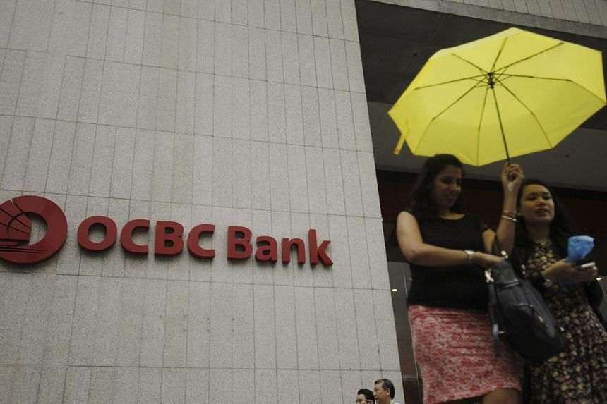 Office workers pass an Oversea-Chinese Banking Corp (OCBC) building in the central business district of Singapore on Jan 6, 2014. OCBC shares fell on Tuesday morning as investors worry it may end up overpaying for its planned acquisition of Hong Kong
