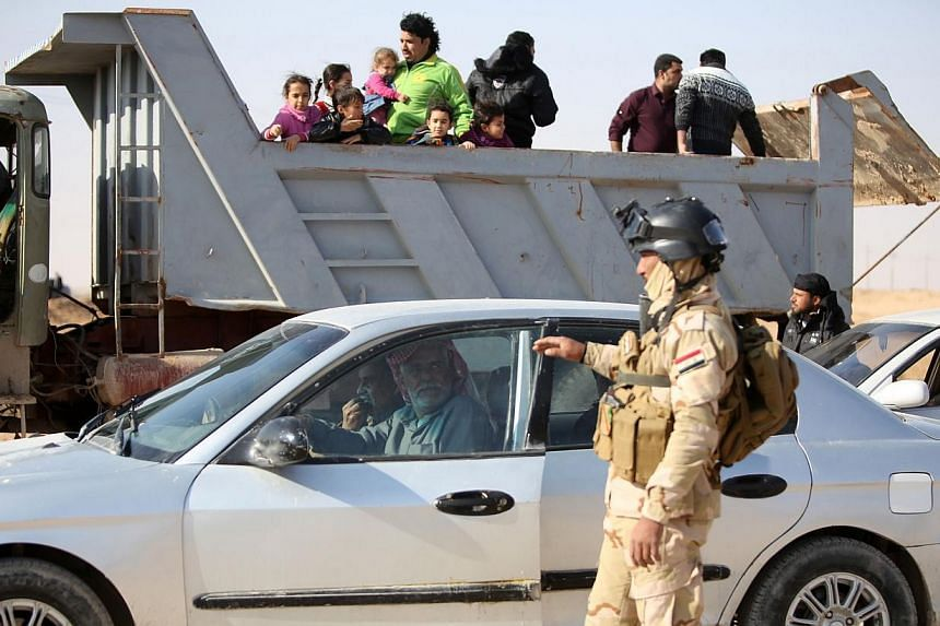 An Iraqi soldier controls vehicles as families, who fled Fallujah, stand in the back of a truck, at an army checkpoint at Ayn al-Tamer crossing at the entrance to Karbala province on Jan 6, 2014.Fighting erupted in Iraq's Fallujah on Jan 8, 201