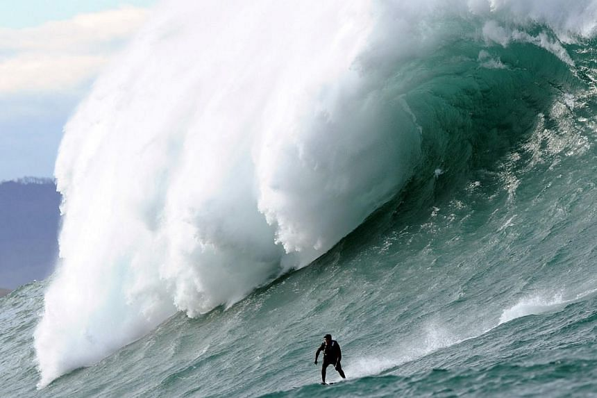 A man surfs the Belharra giant waves, some 2km off the coast of the French basque country town of Urrugne, on Jan 7, 2014. -- PHOTO: AFP