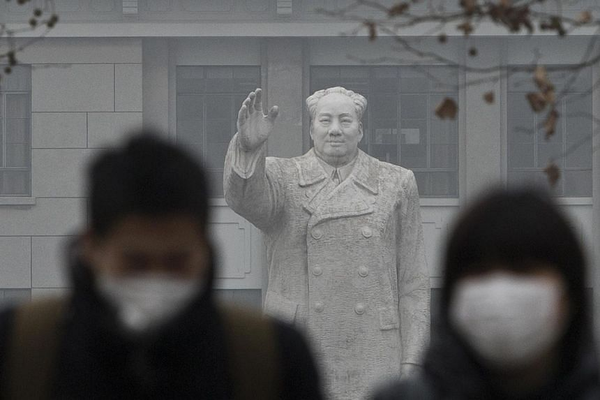 People in masks walking past a statue of late Chinese leader Mao Zedong in downtown Shanghai during a hazy day last December. State media quoted former health minister Chen Zhu as saying that air pollution in China causes premature deaths of 350,000