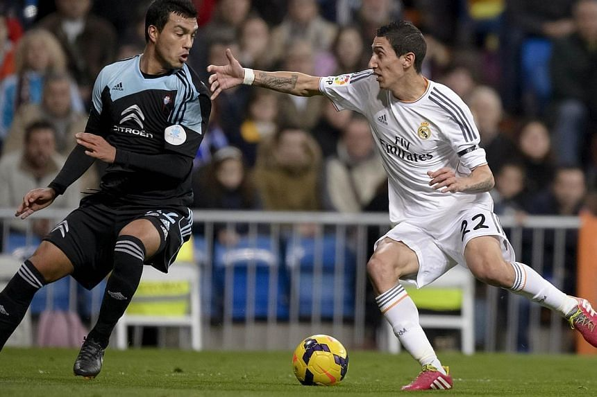 Celta's Argentinian defender Gustavo Cabral (left) vies with Real Madrid's Argentinian midfielder Angel di Maria during the Spanish league football match Real Madrid vs RC Celta de Vigo at the Santiago Bernabeu stadium in Madrid on Jan 6, 2014. Madri