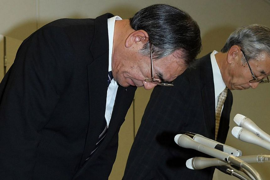 This picture taken on Dec 31, 2013 shows Toshio Kushiro (L), president of Japanese food company Maruha Nichiro Holdings and its subsidiary frozen foods company Aqli Foods president Yutaka Tanabe (R) bowing their heads to apologise at the headquarters