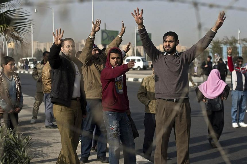 """Supporters of Muslim Brotherhood ousted president Mohamed Morsi flash the """"Rabaa"""" sign behind barbed wire outside the police academy where takes place the second hearing in his murder trial, on Jan 8, 2014 in Cairo. An Egyptian court on Jan 8, 2014,"""