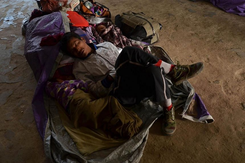 A displaced Rengma Naga tribesman sleeps alongside his child at a relief camp at a school in the Karbi Anglong district of India's north-eastern state of Assam, some 320km from the main city of Guwahati on Jan 7, 2014. Clashes between tribes in India
