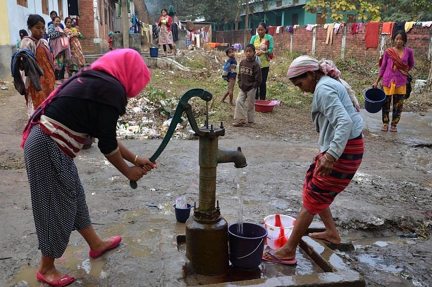 Displaced members of the Rengma Naga tribe use a hand pump at a relief camp at a school in the Karbi Anglong district of India's north-eastern state of Assam on Jan 7, 2014. Clashes between tribes in India's restive north-east Assam state have l