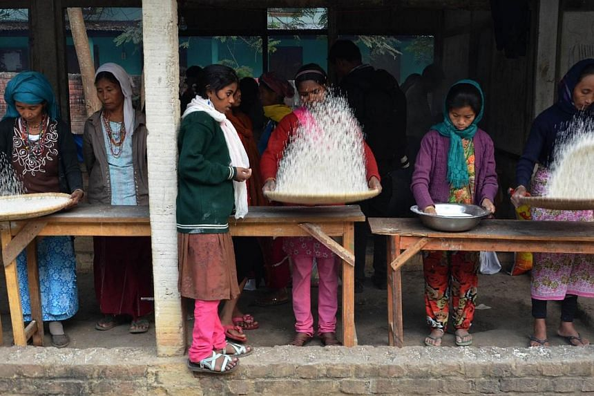 Displaced members of the Rengma Naga tribe use bamboo baskets to clean rice at a relief camp at a school in the Karbi Anglong district of India's north-eastern state of Assam on Jan 7, 2014.Clashes between tribes in India's restive north-east A