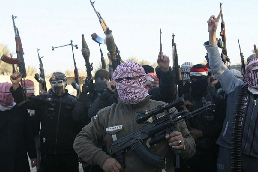 Masked Sunni gunmen chant slogans during a protest against Iraq's Shiite-led government, demanding that the Iraqi army not try to enter the city, in Falluja, 50km west of Baghdad on Jan 7, 2014. They remained in control of Iraq's Fallujah on Jan