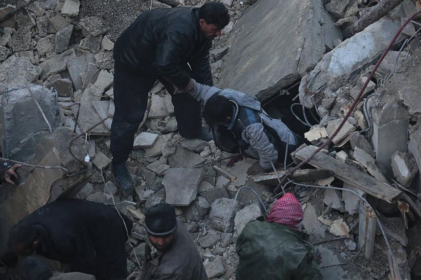 A man helps to pull a person out from under rubble at a site hit by what activists say was an airstrike by forces loyal to Syrian President Bashar al-Assad in the Duma neighbourhood of Damascus, on Jan 7, 2014. Syria's exiled opposition has postponed