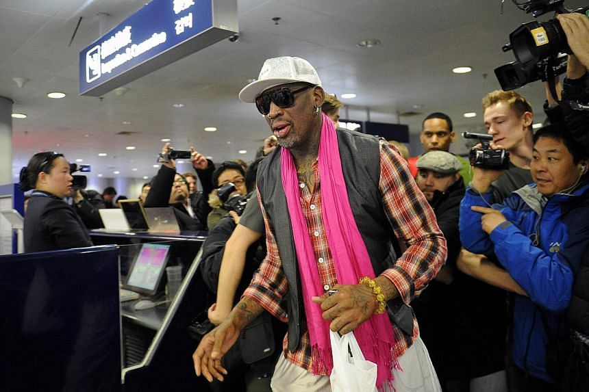 Former NBA basketball player Dennis Rodman of the US (centre) walks past the media to check in for his flight to North Korea at Beijing's international airport on Jan 6, 2014.Rodman, in a television interview on Tuesday, appeared to blame Korea