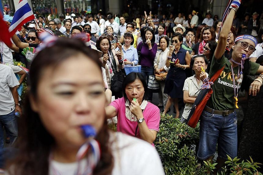 Anti-government protesters blow whistles as they gather in Bangkok's business district on Wednesday, Jan 8, 2014. See more pictures from around the world in Through The Lens' Today in Pictures. -- PHOTO: REUTERS