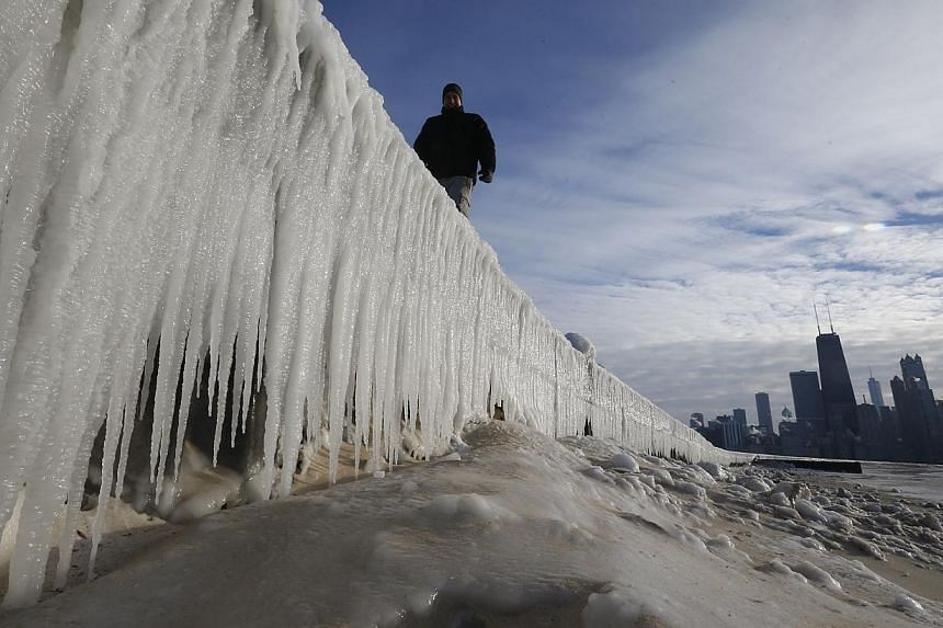 A man walks along a frozen wall on a beach in Chicago, Illinois, on Jan 7, 2014.A deadly chill had much of the United States and Canada in its wintry grip on Tuesday, as a record-breaking cold snap brought temperatures lower than on the surface