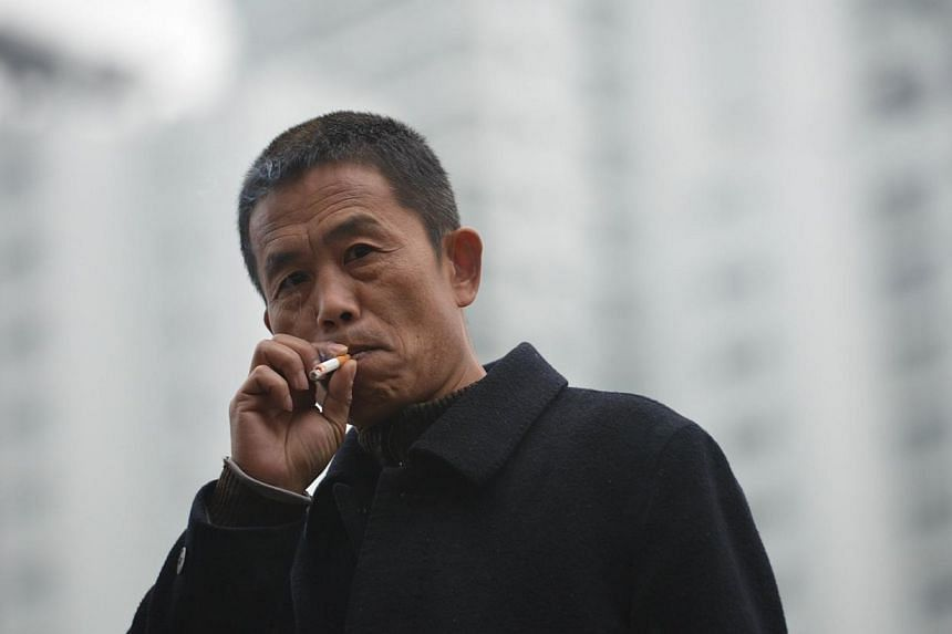 A man smokes a cigarette on a street in Shanghai on Jan 8, 2014.China aims to impose a nationwide ban on smoking in public places this year, as authorities move to stamp out a widespread practice that has taken a severe toll on citizens' health