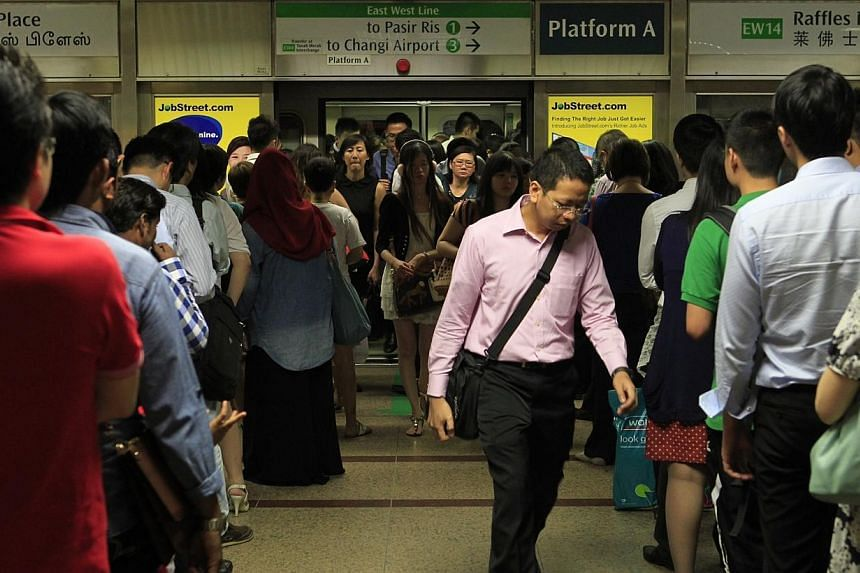 Commuters at Raffles Place MRT station during peak hour on Oct 7, 2013.Rail commuters will be able to stay connected to the Internet on their mobile devices while on the train when Wi-Fi is rolled out at 28 MRT station platforms from the middle