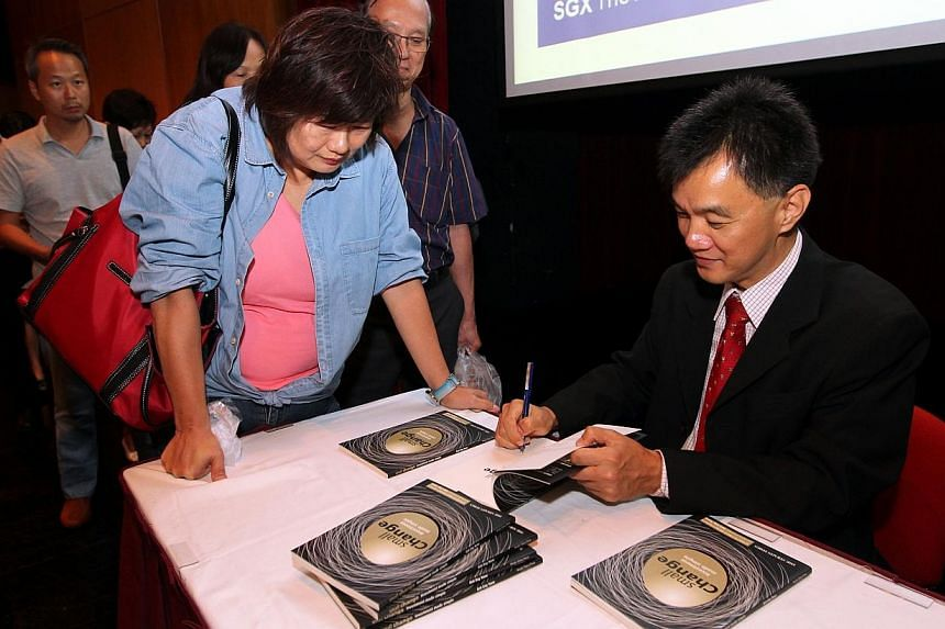 The Straits Times senior correspondent Goh Eng Yeow signs autographs at the launch of his first book, Small Change, Investment Made Simple. More than 220 people turned up at the Wednesday launch of a book written by Mr Goh. -- ST PHOTO: SEA