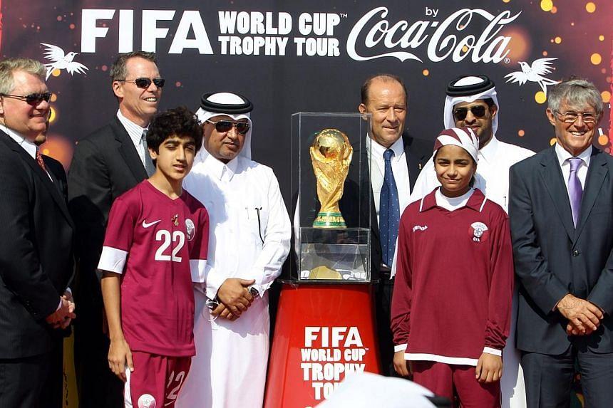 Qatari Saud al-Muhanadi (centre left), secretary general of the Qatar Football Federation, and Fifa representative international coach Gabriel Calderon (centre right) stand next to the Fifa World Cup trophy following its arrival in Doha, on Dec 12, 2