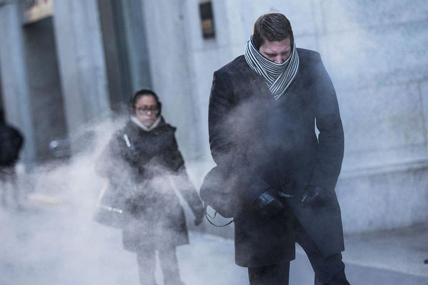 A man clenches his fists while walking past a steam vent on the morning of January 7, 2014 in New York, United States. A polar vortex has descended on much of North America, coming down from the Arctic, bringing record freezing temperatures across mu
