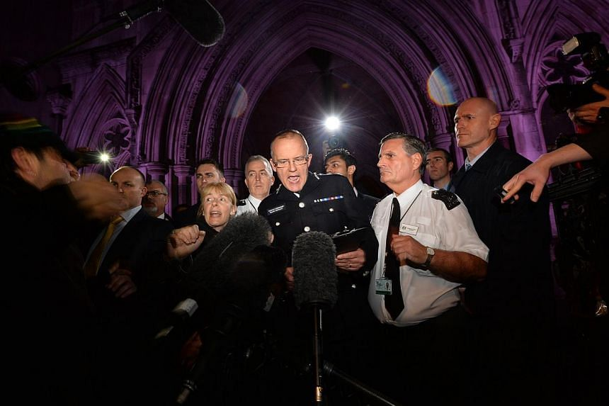 Assistant Commissioner Mark Rowley (centre) addresses the crowd outside the Royal Courts of Justice in London on Jan 8, 2014 after the inquest into the shooting by police of Mark Duggan in 2011 presented its conclusion. A British inquest jury c