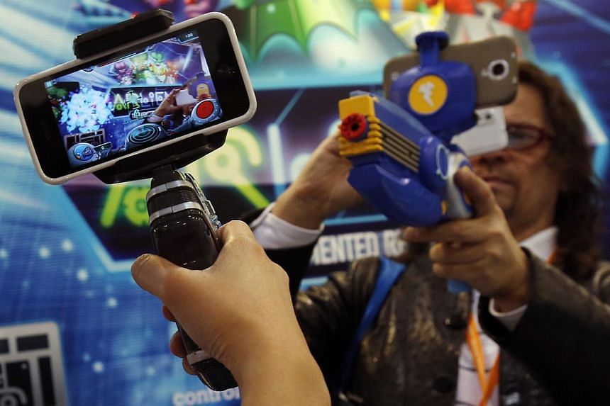 Smartphones are attached to toy guns for a virtual reality shooting game at the Hong Kong Toys and Games Fair on Jan 6, 2014. -- FILE PHOTO: REUTERS