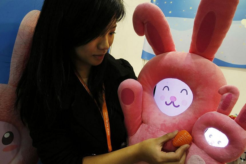 An exhibitor pretends to feed toy rabbits, with their faces powered by an iPad and an iPhone, at the Hong Kong Toys and Games Fair on Jan 6, 2014. -- FILE PHOTO: REUTERS