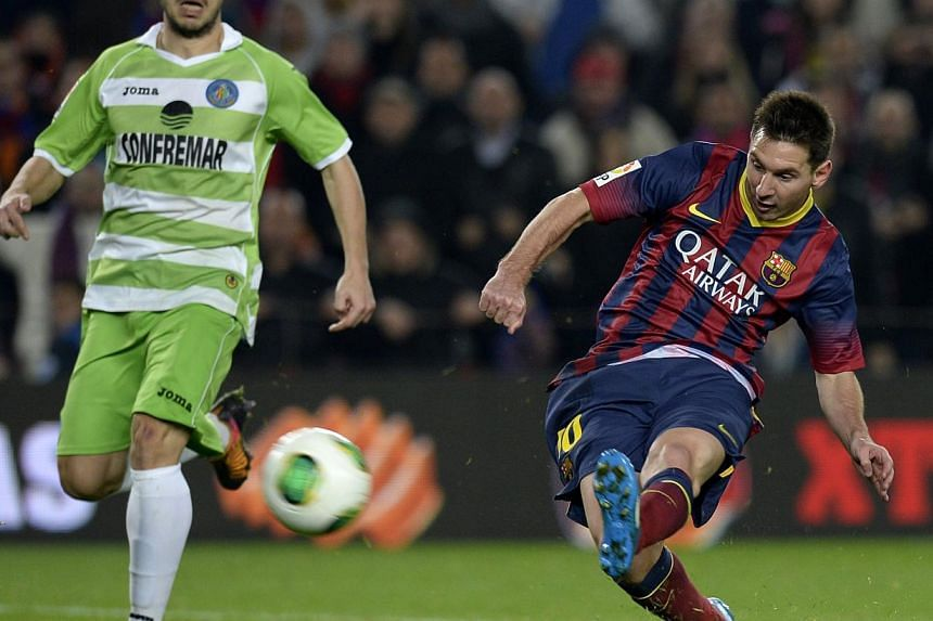 Barcelona's Argentinian forward Lionel Messi putting the ball in the back of the net during the Spanish Copa del Rey (King's Cup) football match against Getafe at the Camp Nou stadium in Barcelona on Jan 8, 2014. -- PHOTO: AFP