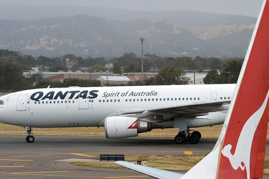 """A Qantas flight taxiing at Adelaide airport on on Dec 10, 2013. Embattled Australian carrier Qantas faces a further increase in its borrowing costs after Moody's downgraded its credit rating to """"junk"""" status on Thursday, just weeks after Standard and"""