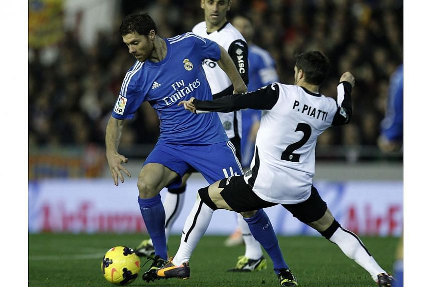 Real Madrid's midfielder Xabi Alonso (left) vies for the ball with Valencia's Argentinian forward Pablo Piatti during the Spanish league football match at the Mestalla stadium in Valencia on Dec 22, 2013. Alonso has ended speculation over his future