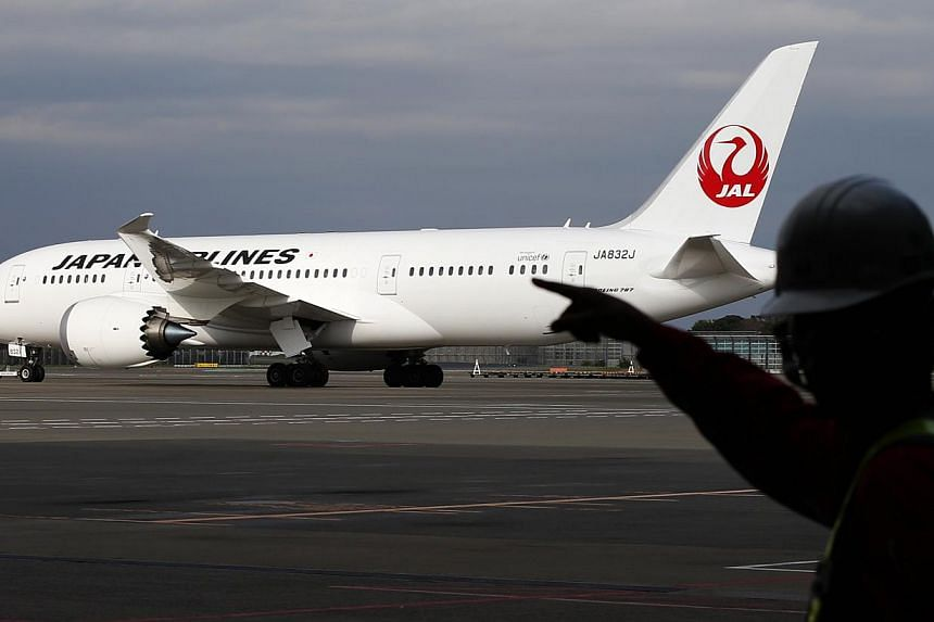 A staff of Japan Airlines' (JAL) walks past one of the company's Boeing Co's 787 Dreamliner plane at Narita international airport in Narita, east of Tokyo, Nov 11, 2013. The United States (US) National Transportation Safety Board (NTSB) said on
