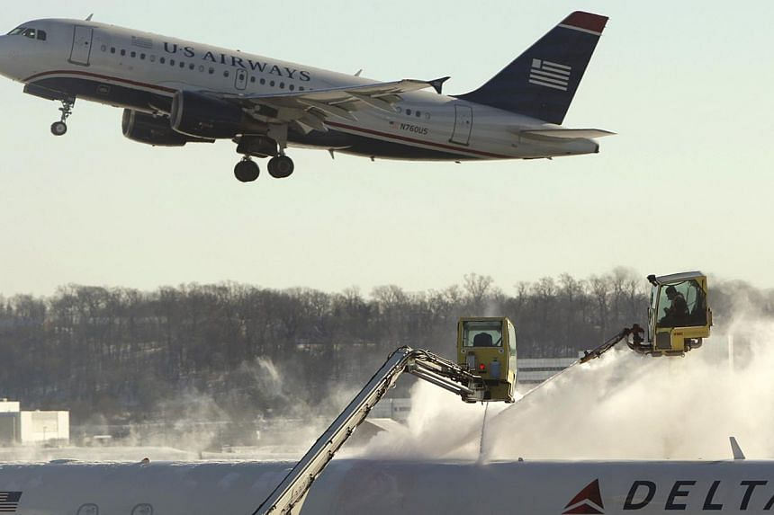 A Delta jetliner (bottom) is de-iced while a US Airways jet takes off at Reagan National Airport in Washington on Jan 3, 2014.Air travel conditions improved in the United States (US) on Wednesday with carriers cancelling fewer flights as wide s