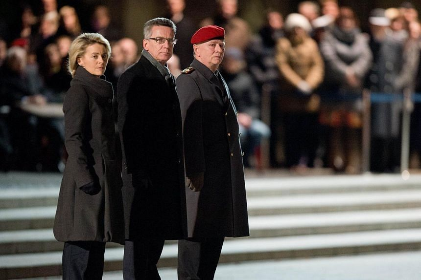 German defence minister Ursula von der Leyen (left) honours former Defence minister Thomas de Maiziere (centre) on Jan 8, 2014 in Berlin during a farewell military ceremony. Mr Maiziereon Wednesday took an unusually undiplomatic parting shot at