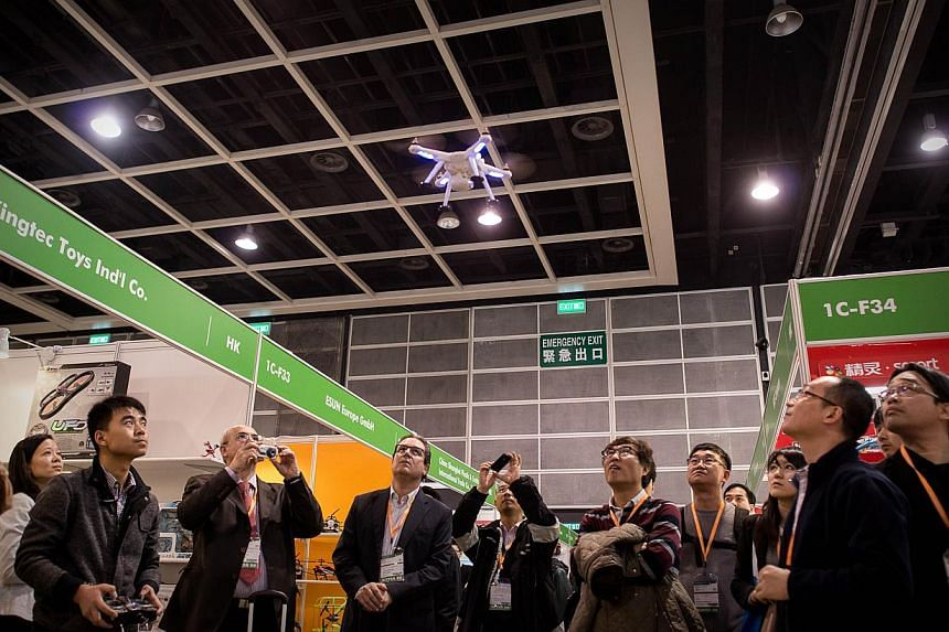 In this picture taken on Jan 8, 2014, a exhibitor flies a drone at the 40th Toys and Games Fair in Hong Kong. Never mind girls and boys - adults who refuse to grow up are being increasingly targeted by a toy industry promoting adolescence as a lifest