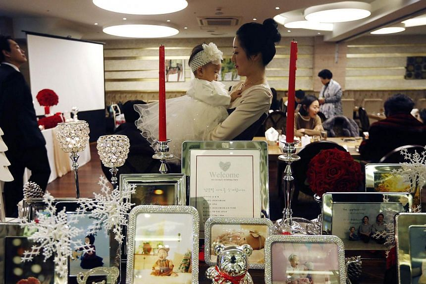 Kim Dot Byul being held by her mother as her pictures are displayed during her first birthday party, or doljanchi in Korean, in Seoul on December 14, 2013. It takes a lot more than a cake and a song to celebrate a baby's first birthday in South Korea