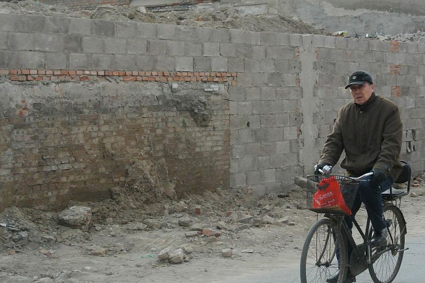 This picture taken on January 7, 2014 shows a man cycling past the demolished Tianyi Inn in Beijing. When they introduced market reforms that would shake the world, China's rulers celebrated a tiny privately owned Beijing hotel that survived decades
