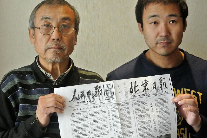 This picture taken on January 7, 2014, shows Mr Qiao Shuzhi (left) and his son Qiao Xuan (right) holding a copy of People's Daily and Beijing Daily front page of 1979, each with an editorial about Tianyi Inn. When they introduced market reforms that