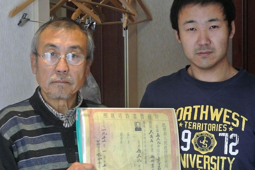 """This picture taken on January 7, 2014, shows Mr Qiao Shuzhi (left) and his son Qiao Xuan (right) posing for a photo with the """"Special Business Operation Licence"""" granted to Qiao's father for running Tianyi Inn in 1953 by Beijing's chief of police. Wh"""